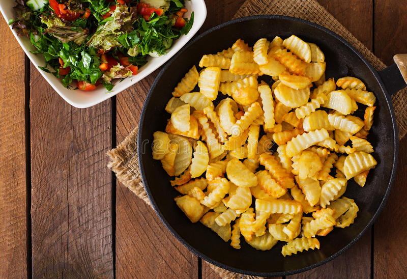 Frying pan with a fried potato in a rural way. On a wooden background. Top view stock photography