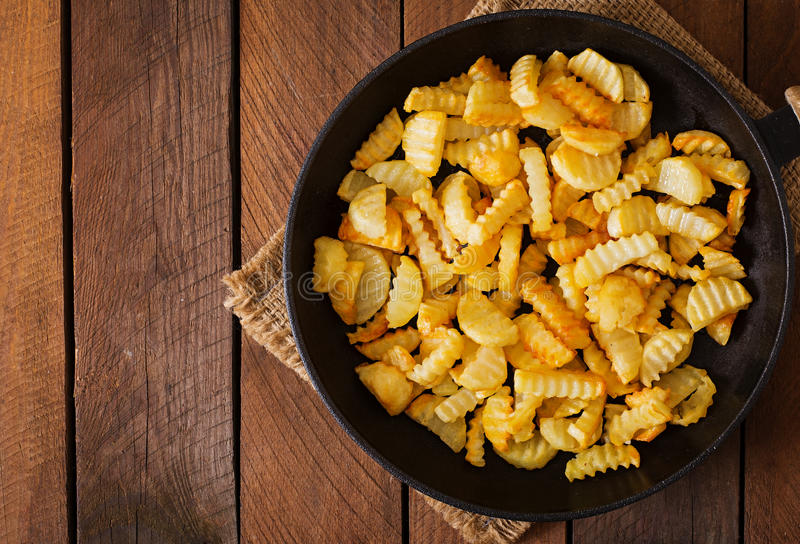 Frying pan with a fried potato in a rural way. On a wooden background. Top view royalty free stock photography