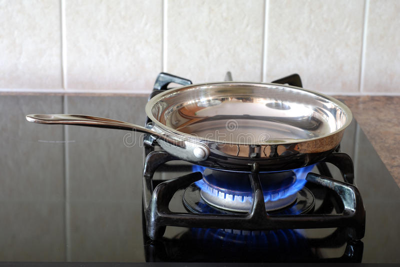 Frying pan on a gas stove stock photography