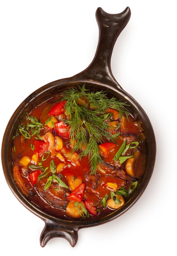 Frying pan with meat. Under a red sauce garnished with dill over white royalty free stock photos