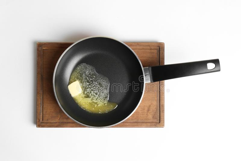 Frying pan with melting butter on board against white background royalty free stock photography