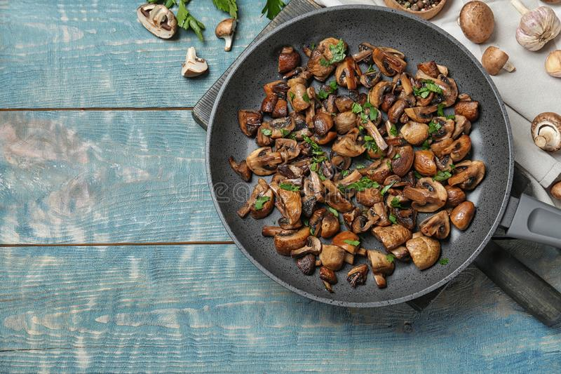 Frying pan of mushrooms on wooden background, top view stock photos