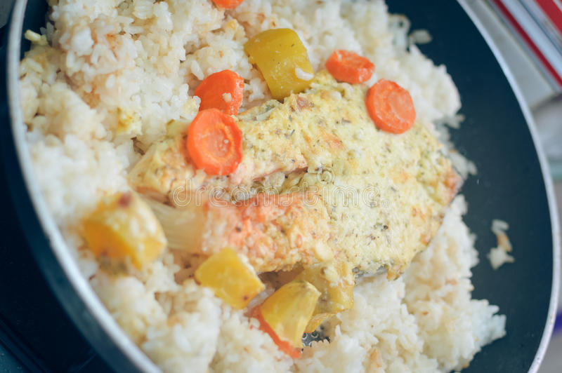 Frying pan with seafood salmon with rice and herbs. Top View. stock image