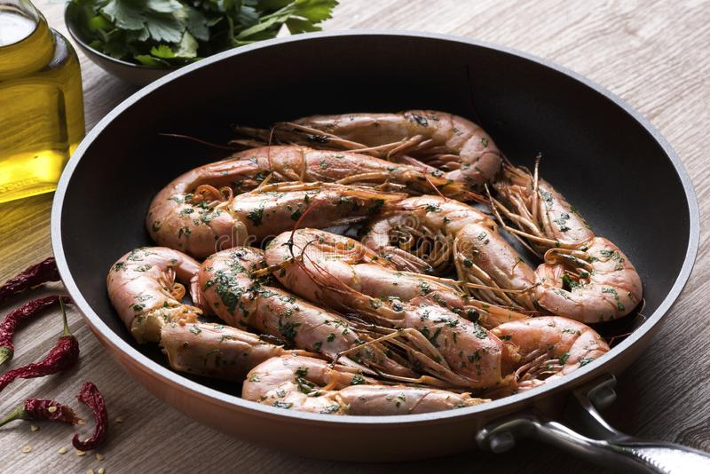 Frying pan with shrimps, oil, garlic and chilli royalty free stock photo