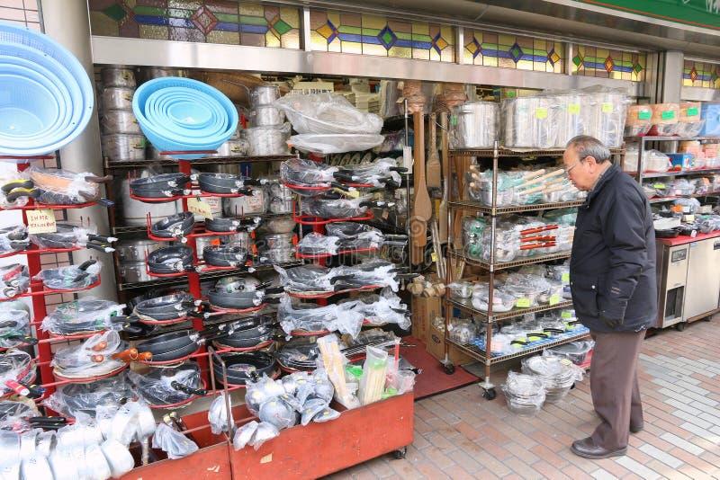 Frying pan store. TOKYO, JAPAN - DECEMBER 4, 2016: Shopper visits specialist frying pan store Kappabashi area of Asakusa in Tokyo, Japan. Kappabashi Street is stock photos