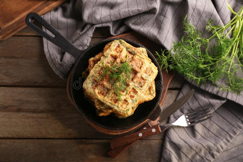 Frying pan with tasty squash waffles on wooden table stock images