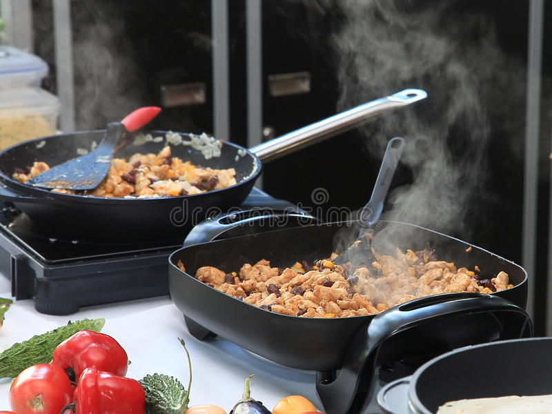 Frying pans. Preparing hot meat food in two frying pans stock images