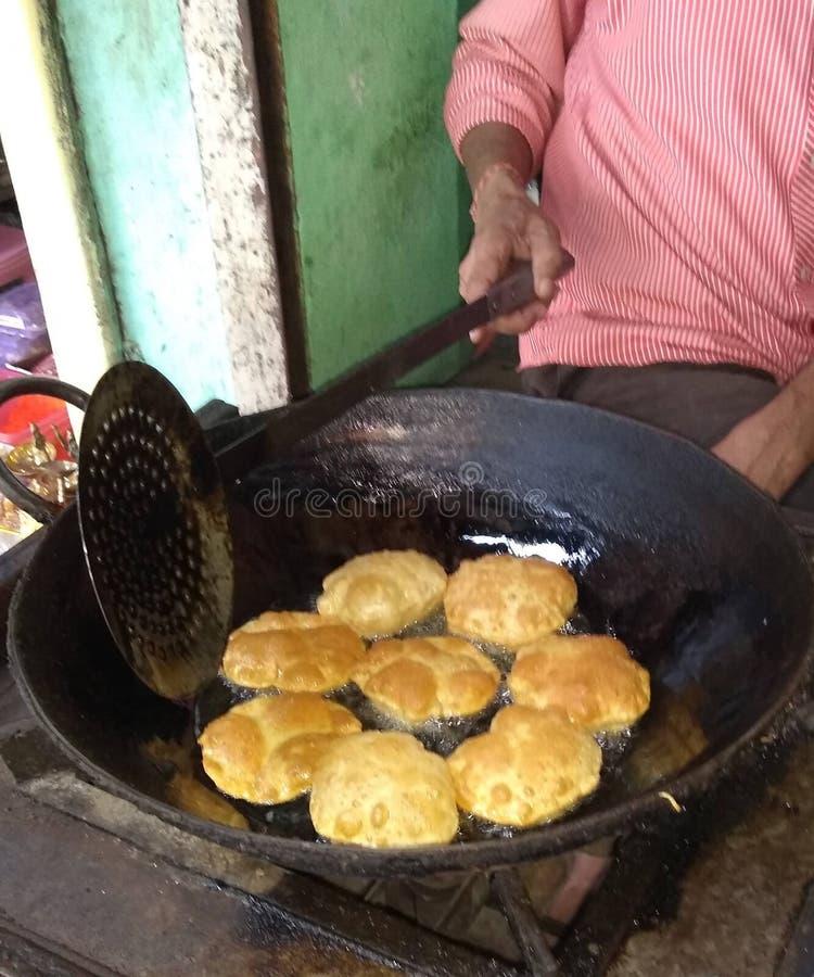 Frying pooris in India stock images