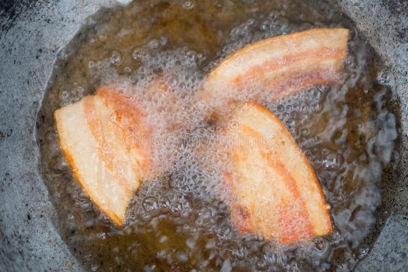 Frying pork belly. In hot oil in pan royalty free stock photography