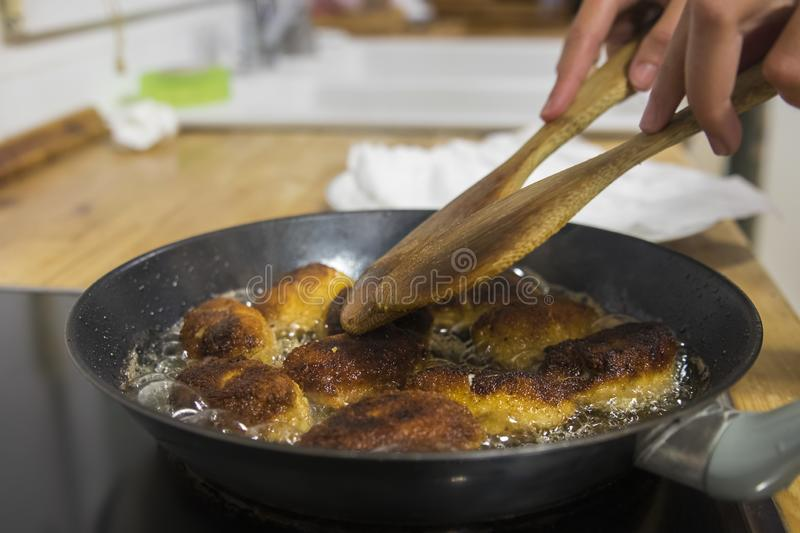Frying spanish homemade croquettes with extra virgin olive oil royalty free stock photography