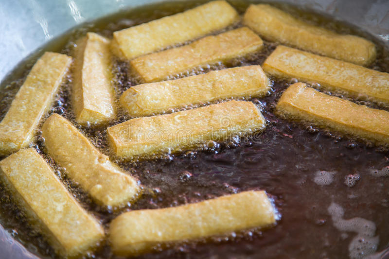 Frying tofu with hot oil in a big pan. asian food. In the market thailand stock images