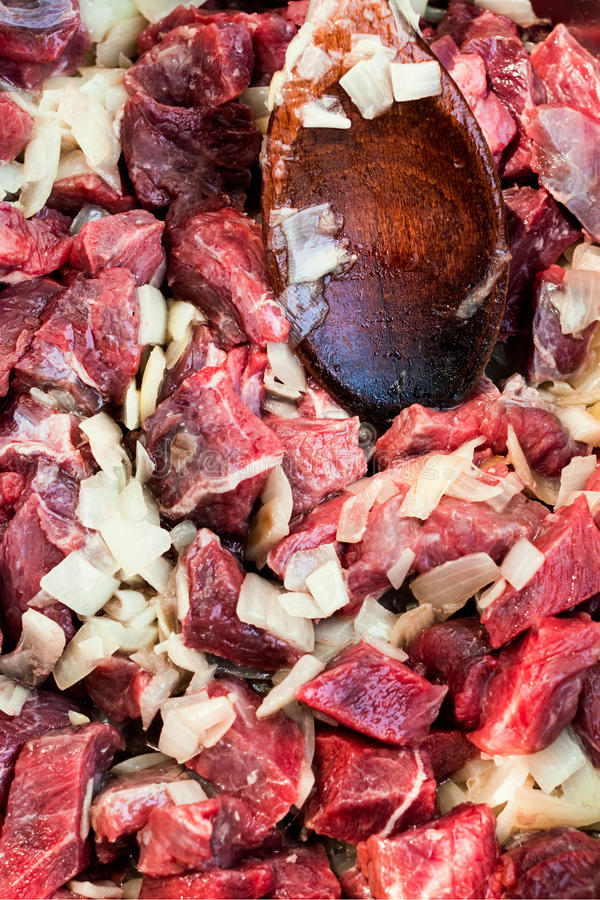 Frying white onions and raw diced wild boar royalty free stock photography