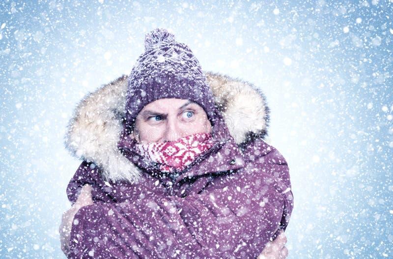 Frysning av mannen i röda vinterkläder täckte armarna omkring sig själv, frost, kall, snöbakgrund royaltyfria bilder