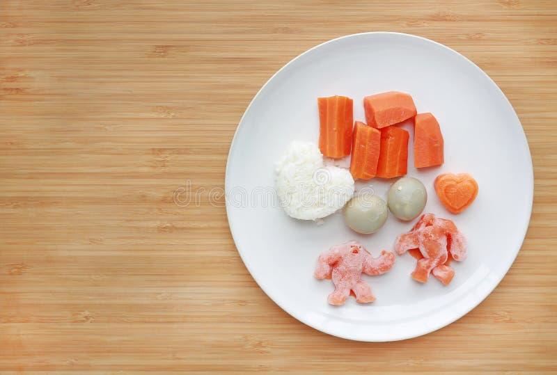 Fryst behandla som ett barn hemlagad mat och råkost i den vita plattan, skivat morotägg och ris för mosat på träbräde arkivfoto