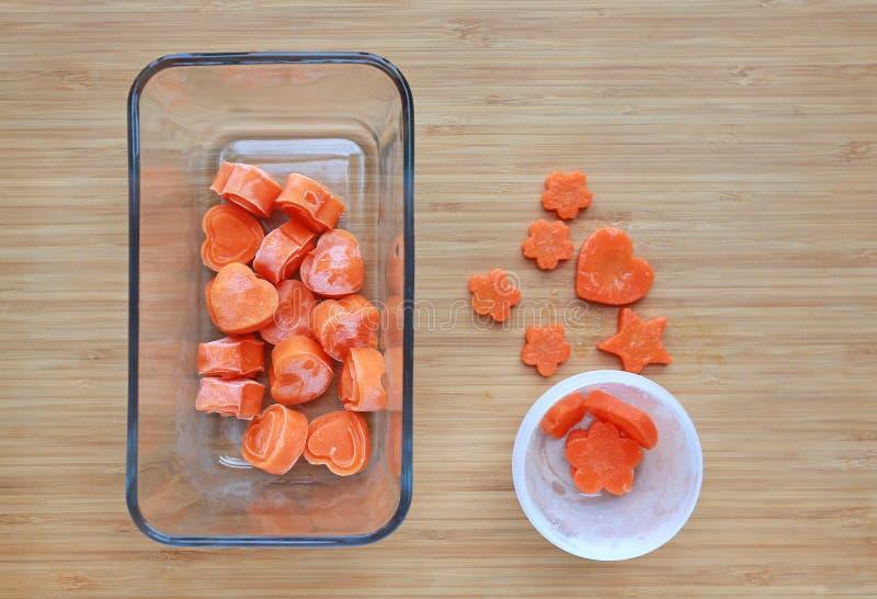Fryst behandla som ett barn hemlagad mat, orange hj?rta fr?n morotkuber i fyrkantig exponeringsglasbunke p? tr?br?de arkivbilder