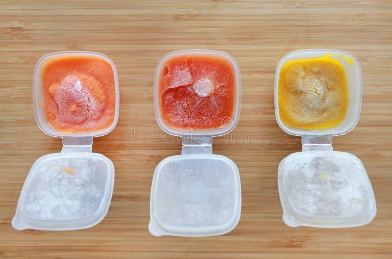 Fryst behandla som ett barn hemlagad, morottomaten och pumpa som mat mosas i fyrkantigt plast- magasin royaltyfri fotografi