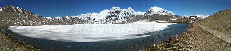 Fryst Gurudongmar sjö som omges av snöig berg som lokaliseras i norr Sikkim arkivfoton