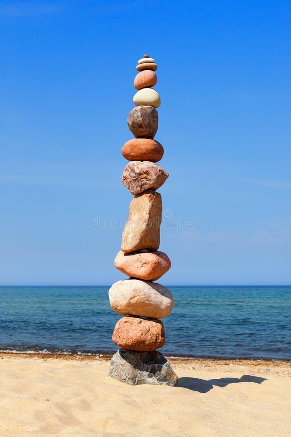 Fryst pyramid av färggranulat på en strand Begreppet balans, harmoni och meditation royaltyfri bild