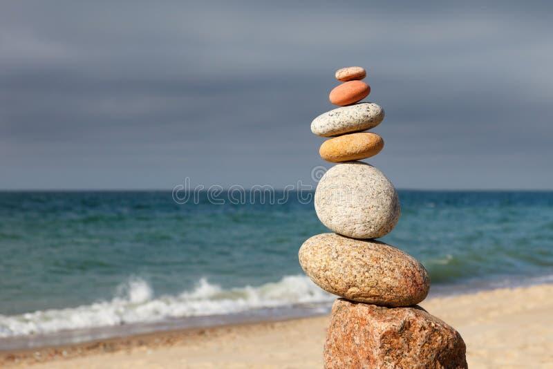Fryst pyramid av färgstarka kulor på en sandstrand på havets bakgrund Begreppet balans, harmoni och meditation royaltyfria foton