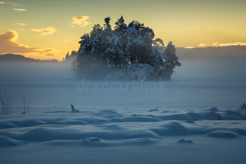 Fryst sjö Jonsvatnet nära Trondheim, Norge Solnedgångljus över annalkande dimma arkivfoton
