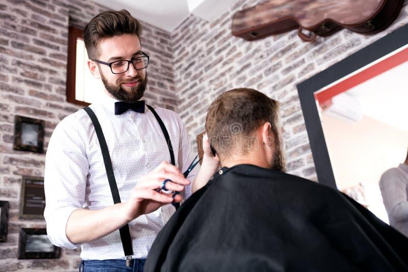 Fryzjer ciie klienta ` s włosy z nożycami fotografia stock