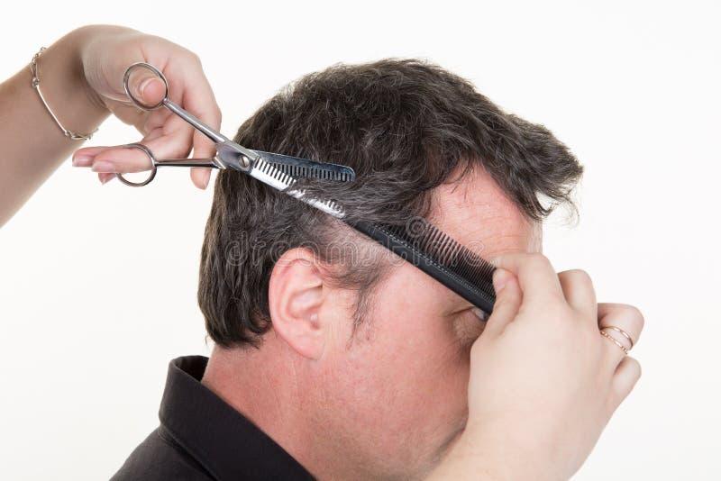 Fryzjer ciie przystojnego młodego człowieka ma ostrzyżenie z nożycami w studiu zdjęcia royalty free