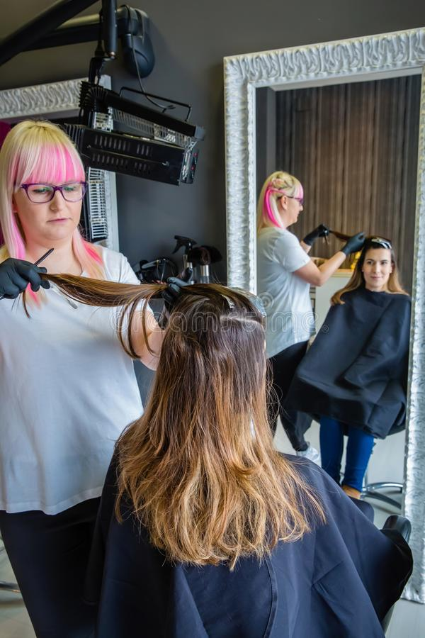 Fryzjer czesze włosy kobieta z czarnymi rękawiczkami fotografia royalty free