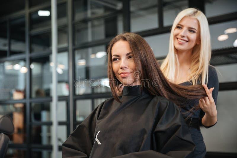 Fryzjer daje nowemu ostrzyżeniu żeński klient przy bawialnią zdjęcia stock