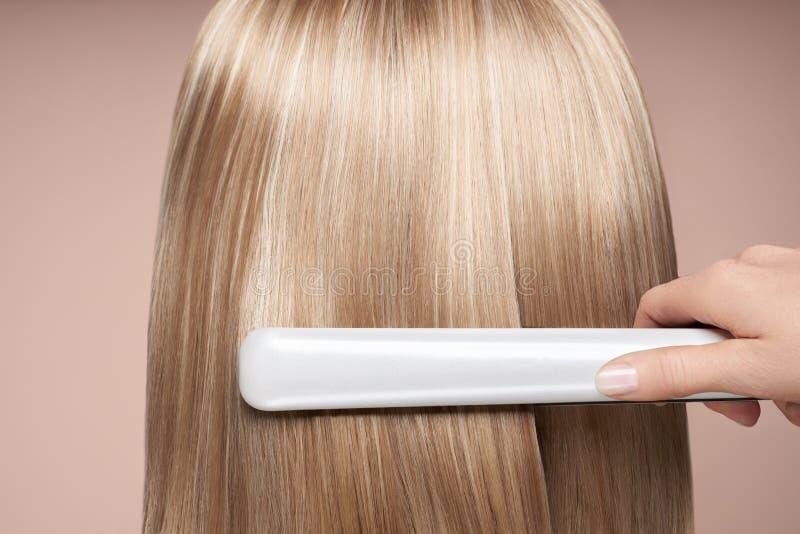 Fryzjer do prostowania długich włosów z żelazkami fotografia royalty free