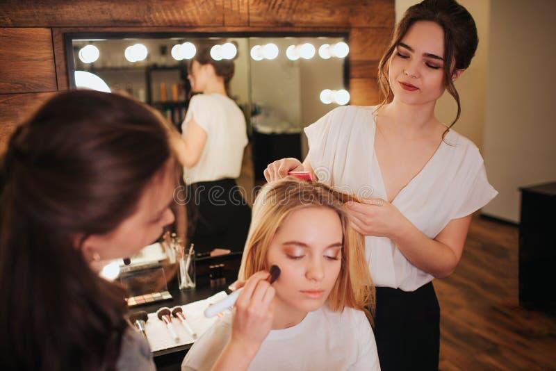 Fryzjer i uzupełnia artysty pracuje wpólnie w piękno pokoju Młody blondynki woamn siedzi na krześle z clossed oczami stosować obraz stock