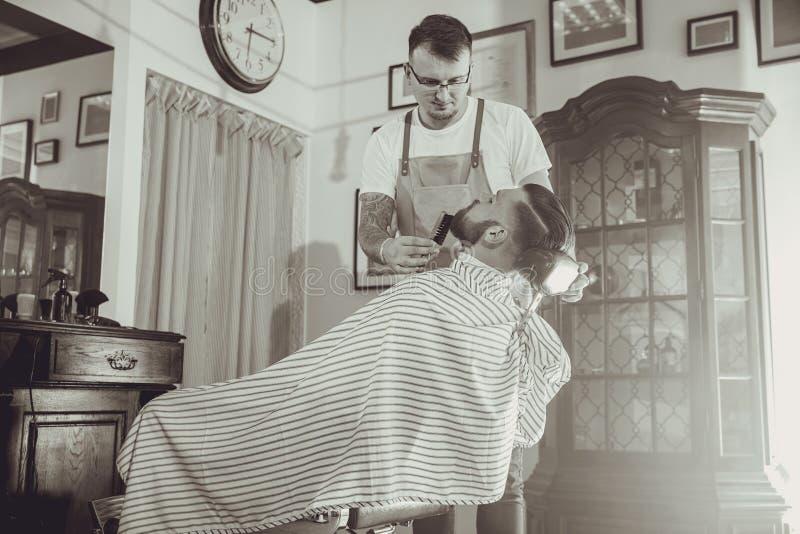 Fryzjer męski podczas pracy w jego fryzjera męskiego sklepie obraz royalty free