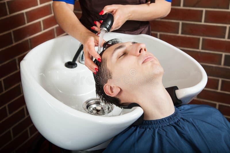 Fryzjer męski przy pracą Fryzjera płuczkowy włosy młody człowiek obrazy royalty free
