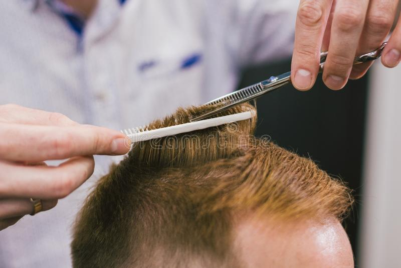 Fryzjer męski Robi ostrzyżeniu Brodatego mężczyzny W zakładzie fryzjerskim Fachowego stylisty klienta tnący włosy w salonie Fryzj zdjęcia royalty free