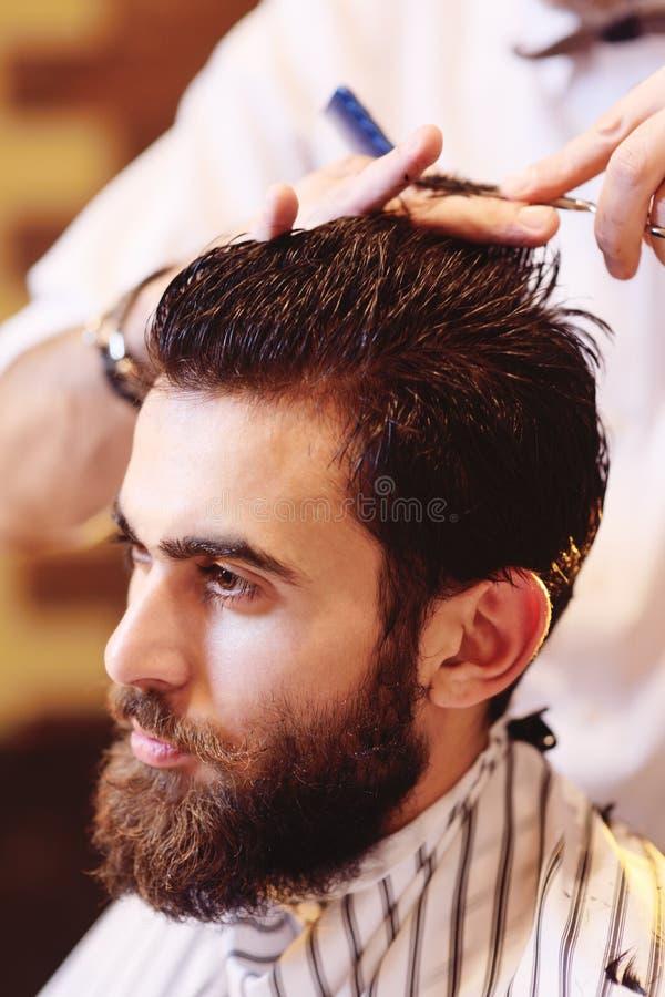 Fryzjer męski robi ostrzyżeniu dla młodego przystojnego mężczyzna z wąsy i brodą zdjęcia royalty free