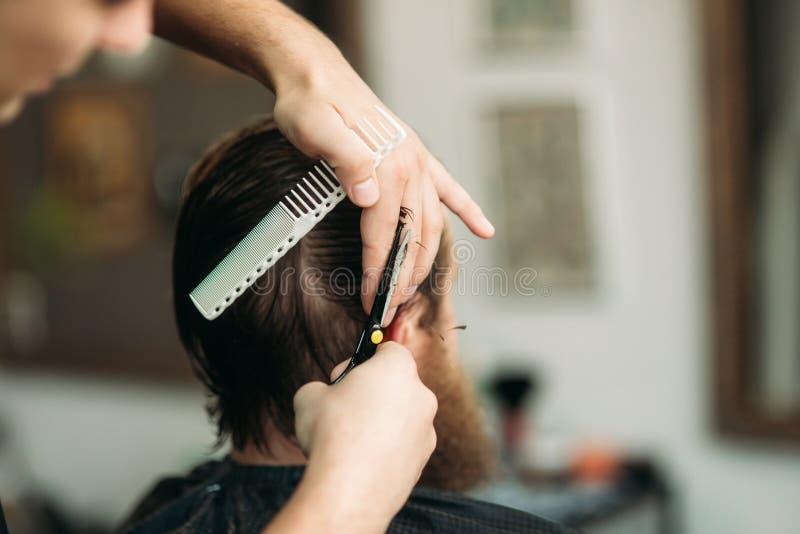 Fryzjer męski używa nożyce i gręplę w zakładzie fryzjerskim fotografia stock