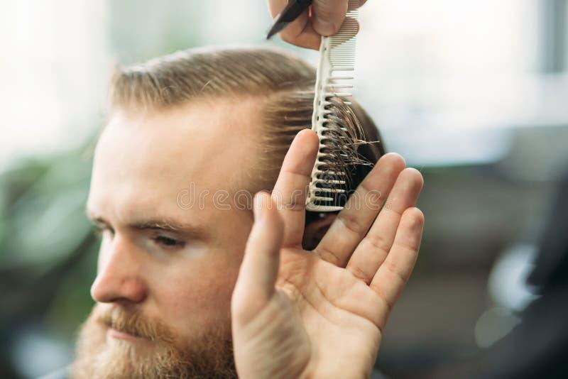 Fryzjer męski używa nożyce i gręplę w zakładzie fryzjerskim obraz royalty free