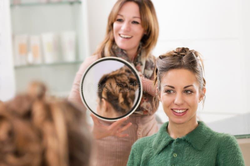 Fryzjer pokazuje klientowi jej włosy zdjęcie stock