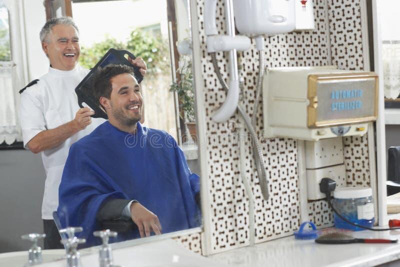 Fryzjer Pokazuje Skończonego ostrzyżenie mężczyzna obraz stock