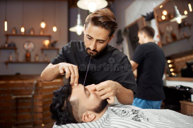 Fryzjer pracuje przy zakładem fryzjerskim, koryguje chleb z białą nicią zdjęcia royalty free