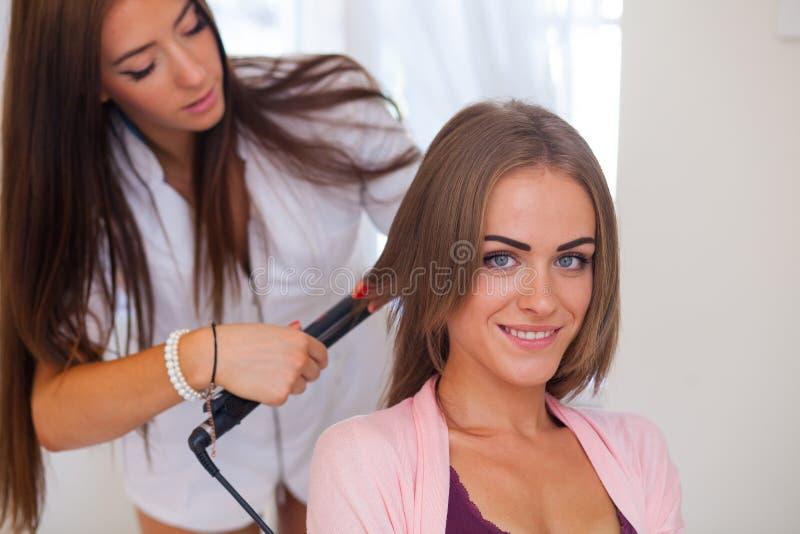 Fryzjer robi ostrzyżeniu dla kobiet w fryzjerstwo salonie fotografia stock