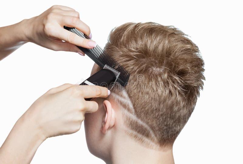Fryzjer robi ostrzyżeniu dla młodego człowieka w zakładzie fryzjerskim fotografia royalty free