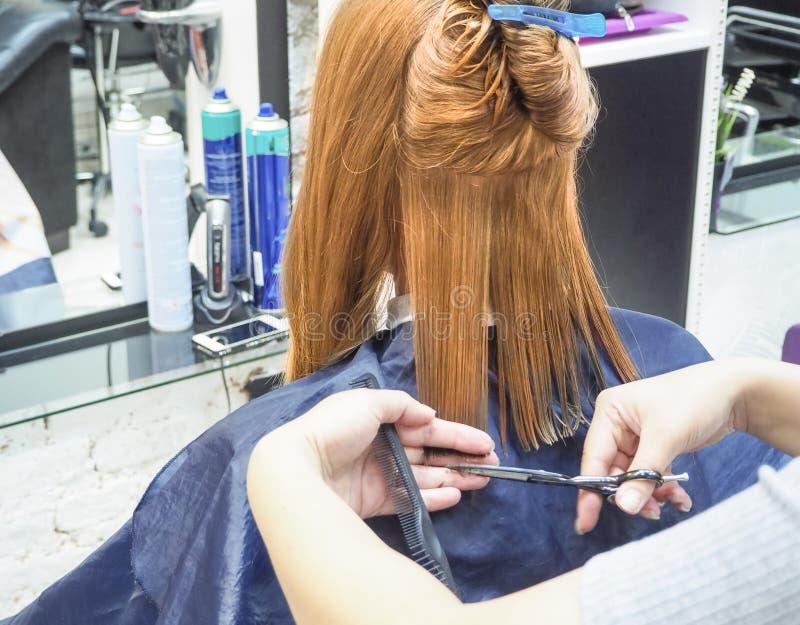 Fryzjer robi ostrzyżeniu w fryzjerstwo salonie tnący włosiany fryzjer wręcza s narzędzi kobiety Piękno przemysł obraz royalty free