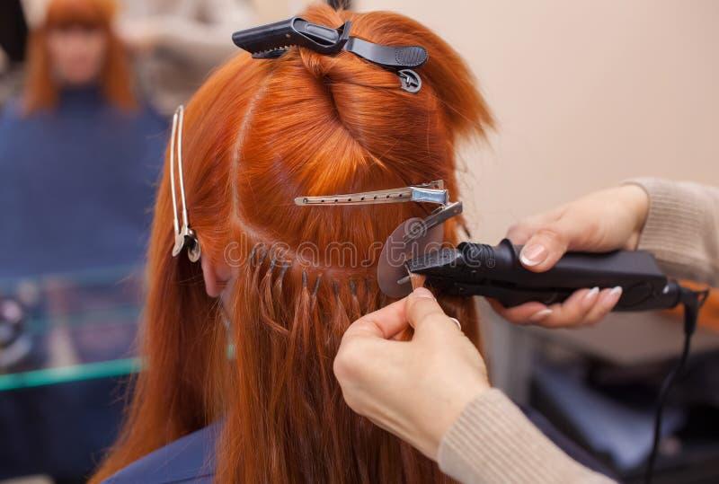 Fryzjer robi włosianym rozszerzeniom młoda, miedzianowłosa dziewczyna w piękno salonie, zdjęcie royalty free