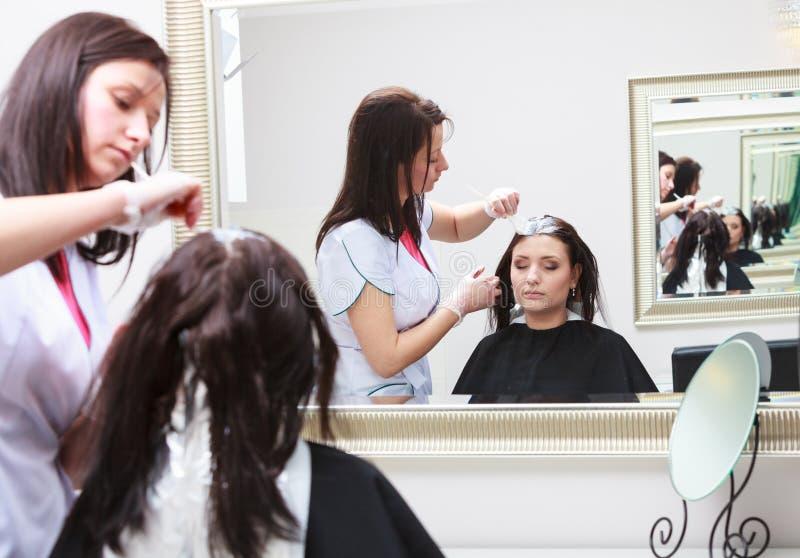 Fryzjer stosuje koloru żeńskiego klienta przy salonem, robi włosianemu barwidłu obraz royalty free
