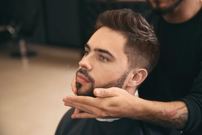 Fryzjer stosuje serum na klient brodzie w zakładzie fryzjerskim Fachowy golenie obrazy royalty free