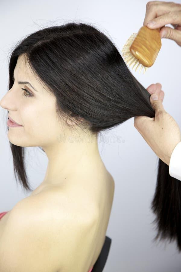 Fryzjer szczotkuje pięknego silky długiego czarni włosy zdjęcia royalty free