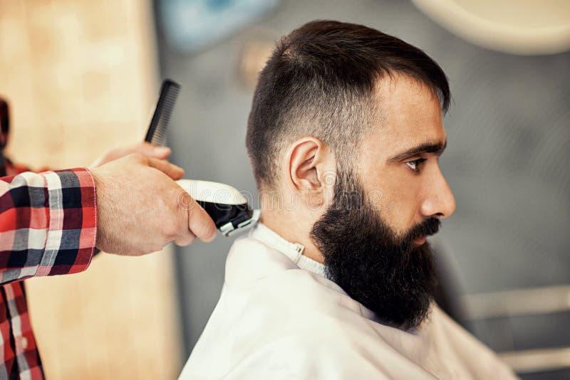 Fryzjer w fryzjera męskiego sklepu modnisia rżniętym włosy zdjęcie royalty free