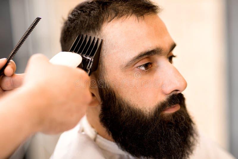 Fryzjer w fryzjera męskiego sklepu modnisia rżniętym włosy z włosianą drobiażdżarką zdjęcie stock