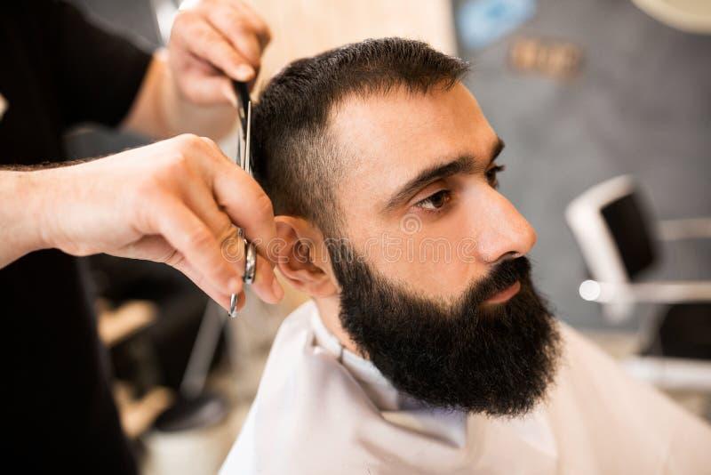 Fryzjer w fryzjera męskiego sklepu rżniętym włosy z nożycami i gręplą obrazy stock