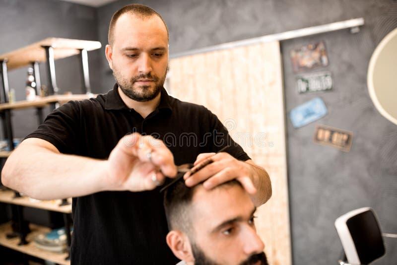 Fryzjer w fryzjera męskiego sklepu rżniętym włosy z nożycami i gręplą cl obraz stock